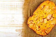 被烘烤的饼顶视图用在麻袋布的苹果在白色木背景 土气样式 免版税库存照片