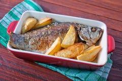 被烘烤的鱼和土豆 免版税库存照片