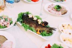 被烘烤的鱼用柠檬装饰用不同的菜 婚礼桌集合 图库摄影