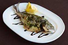 被烘烤的鱼用调味汁和柠檬 库存图片