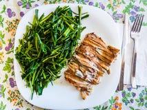 被烘烤的鲥鱼盘用苦苣生茯 库存图片