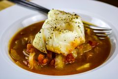 被烘烤的鳕鱼用蕃茄、茴香和葱 免版税库存图片