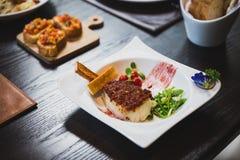 被烘烤的鳕鱼用调味汁,平底锅烤了婴孩菜、豌豆和蕃茄供食用面包条 库存图片