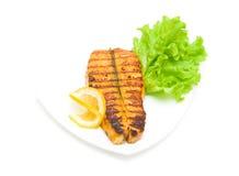 被烘烤的鳟鱼、柠檬和莴苣在白色背景 库存图片