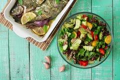 被烘烤的鳟鱼和新鲜的沙拉在明亮的木背景 库存照片