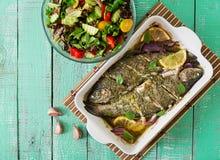 被烘烤的鳟鱼和新鲜的沙拉在明亮的木背景 免版税图库摄影