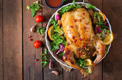 被烘烤的鸡充塞用圣诞晚餐的米在一张欢乐桌上 免版税库存图片