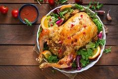 被烘烤的鸡充塞用圣诞晚餐的米在一张欢乐桌上 图库摄影