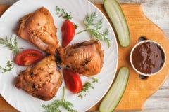 被烘烤的鸡大腿、菜和调味汁在木背景 库存照片