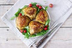 被烘烤的鸡大腿与装饰芝麻菜和蕃茄 土气样式,选择聚焦 库存图片