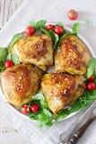 被烘烤的鸡大腿与装饰芝麻菜和蕃茄 土气样式,选择聚焦 免版税库存照片
