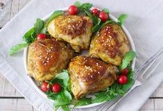 被烘烤的鸡大腿与装饰芝麻菜和蕃茄 土气样式,选择聚焦 库存照片
