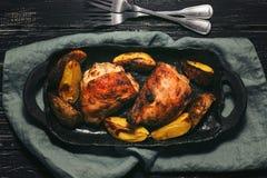 被烘烤的鸡大腿用在一个土气盘的土豆 黑暗的背景,顶视图,平的位置 免版税库存图片