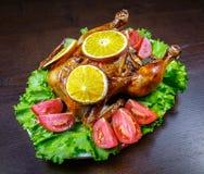 被烘烤的鸡用桔子和新鲜的蕃茄 免版税图库摄影