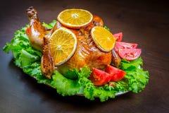 被烘烤的鸡用桔子和新鲜的蕃茄 免版税库存图片