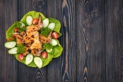 被烘烤的鸡翼用蔬菜沙拉在一张木桌,特写镜头视图离开 在视图之上 文本的空间 免版税库存照片