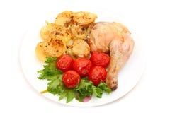 被烘烤的鸡腿用土豆和蕃茄 免版税库存图片