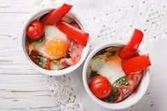 被烘烤的鸡蛋用菠菜、胡椒、蕃茄和乳酪在杯子分类 免版税库存图片