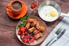 被烘烤的鸡蛋用香肠和菜在平底锅 库存照片