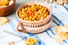 被烘烤的鸡豆用在土气背景,熏制的辣椒粉的香料 免版税库存图片