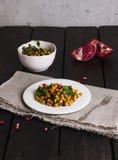 从被烘烤的鸡豆的沙拉,石榴,在白色pla的荷兰芹 库存照片
