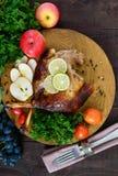 被烘烤的鹅腿,服务用苹果,菜,葡萄,在一个圆的橡木盘子的绿色 免版税库存图片