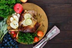 被烘烤的鹅腿,服务用苹果,菜,葡萄,在一个圆的橡木盘子的绿色 库存照片
