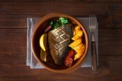 被烘烤的dorado用新鲜的沙拉和菜 顶视图 布朗木桌 图库摄影