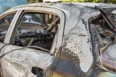 被烧光的汽车特写镜头在街道上的 库存照片