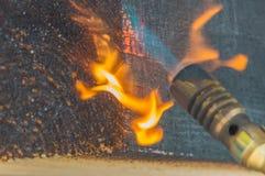 被烧焦的木材对待与从煤气喷燃器的火 免版税图库摄影