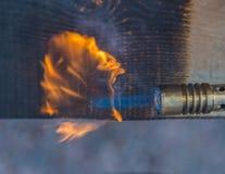 被烧焦的木头对待与从煤气喷燃器的火 库存照片