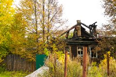 被烧的传统俄国木房子izba在秋天 免版税库存图片