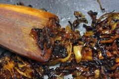 被烧的葱照片在聚四氟乙烯平底锅和木小铲的 被损坏的不健康的被煮过头的被烧的膳食 葱令人厌恶的残羹剩饭 免版税库存照片