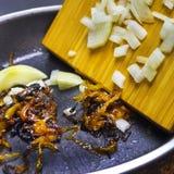 被烧的葱照片在聚四氟乙烯平底锅和木小铲的 被损坏的不健康的被煮过头的被烧的膳食 葱令人厌恶的残羹剩饭 库存照片