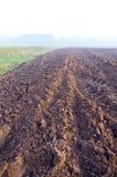 被犁的秋天农田和薄雾 免版税库存照片