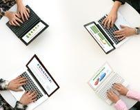 被环绕的书桌顶视图有键入在键盘的四只膝上型计算机和人手的 免版税库存图片