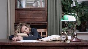 被用尽的女性睡着的在堆书在她的书桌和叫醒由警报迅速采取她书和 免版税库存图片