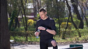被用尽的慢跑者饮用水的慢动作从瓶的在完成他的训练以后在公园 股票视频