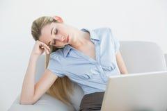 被用尽的ponytailed女实业家坐长沙发睡觉 库存照片