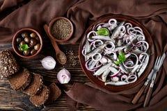 被盐溶的西鲱用了卤汁泡与在陶器板材的红洋葱圆环 芫荽子、棕色布料、叉子和刀子在老 免版税库存图片