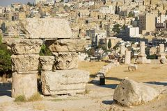 被破坏的专栏的古老石块在阿曼城堡的有城市的背景的在阿曼,约旦 免版税图库摄影