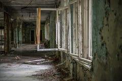 被破坏的大厅阴沉的看法有残破的窗口的在Pripyat学校 免版税库存照片