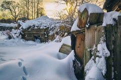 被破坏的房子在被放弃的俄国村庄在多雪的冬天 库存照片