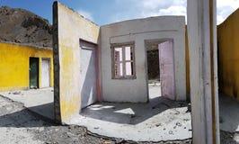 被破坏的房子墙壁没有一个屋顶,黄色,桃红色和白色表面的与窗口和门,蓝天空的开口  免版税图库摄影