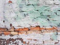 被破坏的砖墙,被绘的白色与浅绿色和镶边桔子,葡萄酒背景斑点  库存图片