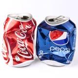 被碰撞的可乐和百事可乐罐头 库存图片