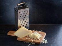 被磨碎的帕尔马干酪在片断和和在a的一台使用的金属磨丝器 库存照片