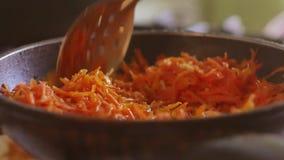 被磨碎的红萝卜在向日葵油的一个煎锅油煎 素食主义户内被磨碎的食物红萝卜 股票视频