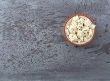 被粉碎的青纹干酪的部分在a的在灰色背景抵消的一个小碗 免版税库存图片
