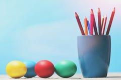 被绘的复活节彩蛋和五颜六色的铅笔在蓝色杯子设置了 库存图片